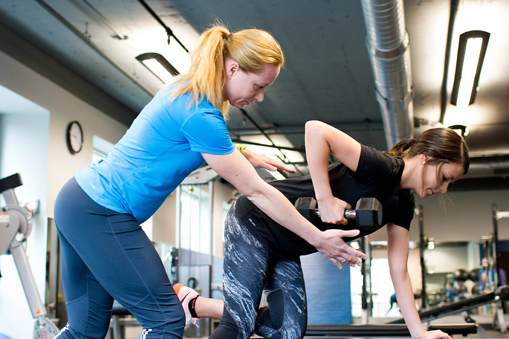 A personal trainer helping a client with free weights